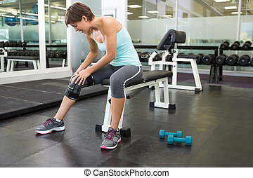 Fit brunette sitting on bench holding injured knee at the...