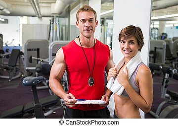 Handsome personal trainer with his client smiling at camera...