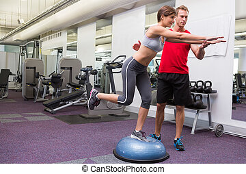 Personal trainer with client on bosu ball at the gym