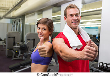 Fit attractive couple smiling at camera showing thumbs up at...