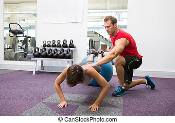 Personal trainer with client doing push up on exercise ball...