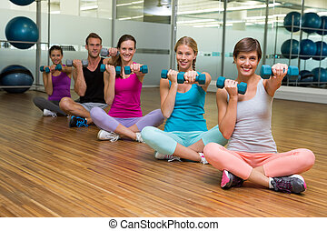 Fitness class sitting and holding dumbbells at the gym