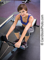Fit smiling brunette working out on rowing machine at the...