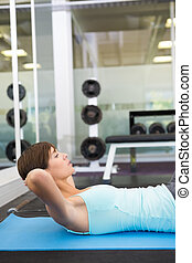 Fit brunette doing sit up on exercise mat at the gym