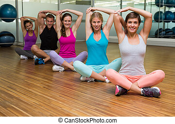 Fitness class sitting and stretching at the gym