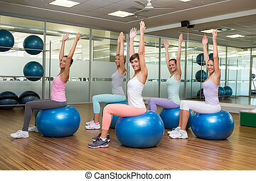 Fitness class sitting on exercise balls in studio at the gym