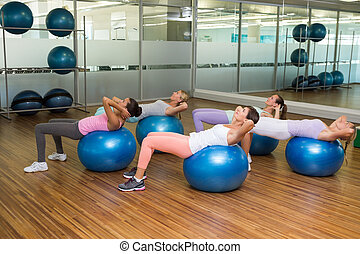 Fitness class doing sit ups on exercise balls in studio at...