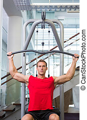 Strong man using weights machine for arms at the gym