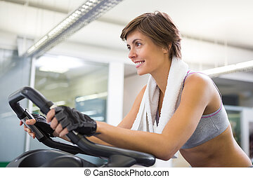 Fit smiling woman working out on the exercise bike at the...