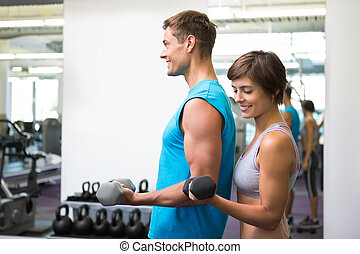 Fit happy couple lifting dumbbells together at the gym