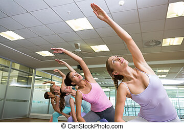 Yoga class in extended triangle pose in fitness studio at...