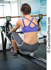 Fit brunette working out on rowing machine