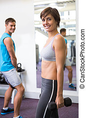 Fit couple lifting weights together smiling at camera at the...