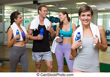 Fit woman smiling at camera in busy fitness studio at the...