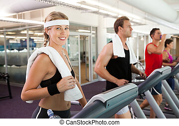 Row of people working out on treadmills at the gym