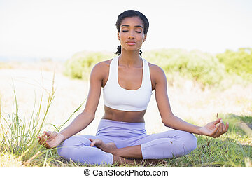 Fit woman sitting on grass in lotus pose with eyes closed on...