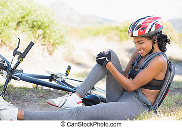 Fit woman holding her injured knee after bike crash on a...