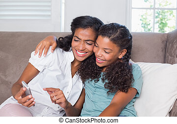 Happy mother and daughter using smartphone together on sofa...