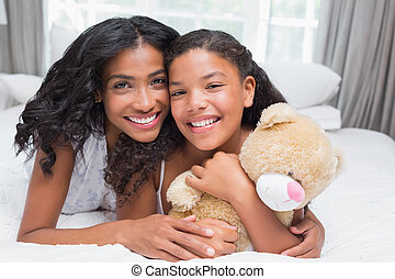 Pretty woman lying on bed with her daughter smiling at...
