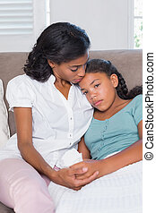 Concerned mother cuddling sick daughter at home in living...