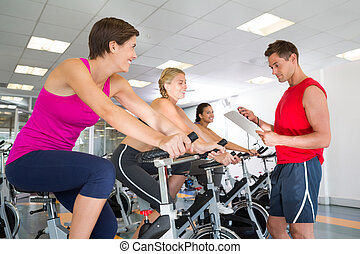 Trainer talking with his spin class at the gym