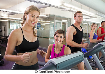 Trainer and clients smiling at camera on the treadmill at...