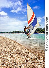 Wind Surfing - Windsurfer surfing on a beautiful lake near...