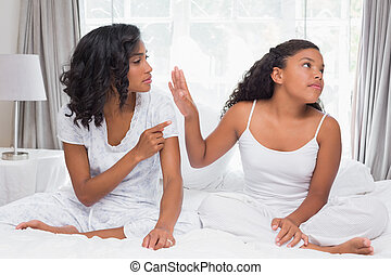 Mother and daughter having an argument on bed at home in...