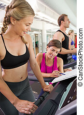 Trainer talking to her client on the treadmill at the gym