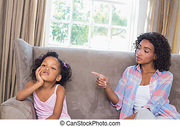 Pretty mother scolding her daughter on the couch at home in...