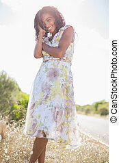 Beautiful woman in floral dress smiling at camera on a sunny...