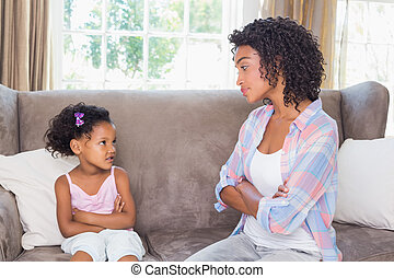 Pretty mother sitting on couch with petulant daughter at...