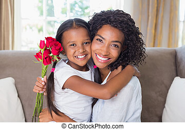 Pretty mother sitting on the couch with her daughter holding...