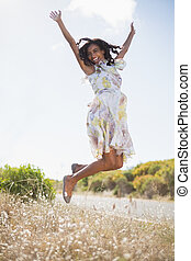 Happy pretty woman jumping up in floral dress on a sunny day...