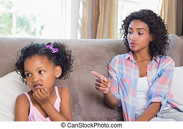 Pretty mother sitting on couch scolding petulant daughter at...