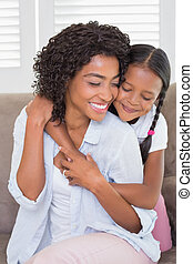 Pretty mother sitting on the couch with her daughter hugging