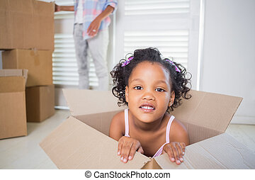 Cute daughter sitting in moving box in new home