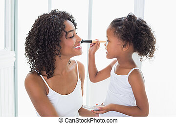 Cute daughter putting makeup on her mothers face at home in...