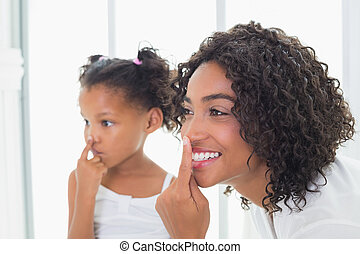 Pretty mother putting face cream on with her daughter at...