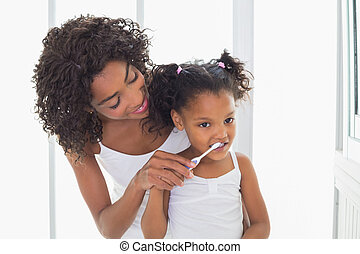 Pretty mother helping her daughter brush her teeth at home...