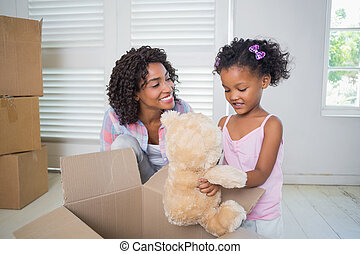 Cute daughter unpacking her teddy bear with mother in their...