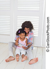 Mother and daughter sitting on the floor reading storybook...