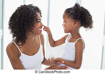Cute daughter putting face cream on mothers nose at home in...