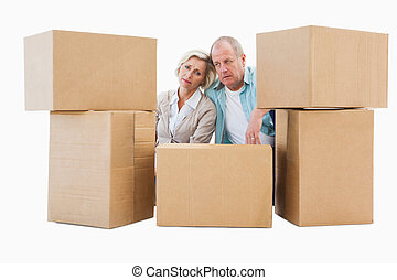 Stressed older couple with moving boxes on white background