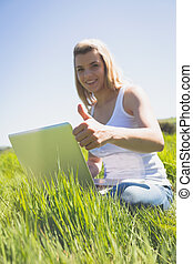 Pretty blonde sitting on grass using her laptop smiling at camer