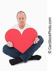 Upset man sitting holding heart shape on white background