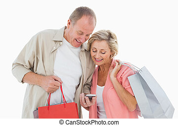 Smiling older couple holding shopping bags looking at...