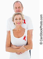 Mature couple supporting aids awareness together on white...