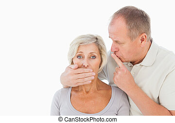 Man silencing his fearful partner on white background