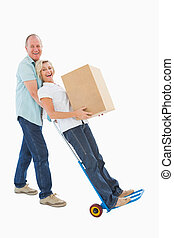 Fun older couple holding moving boxes on white background